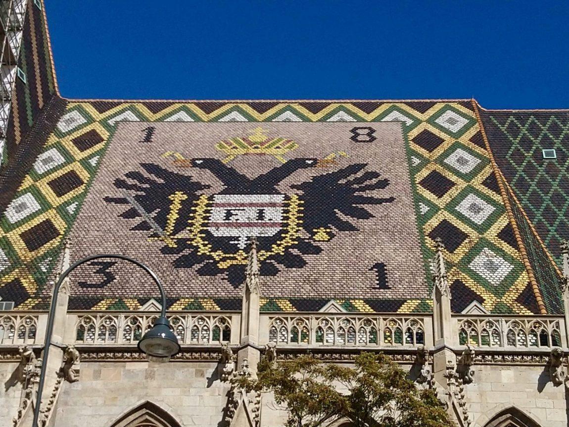 Sobre el tejado de la Catedral de San Esteban el escudo del desaparecido Imperio austríaco...